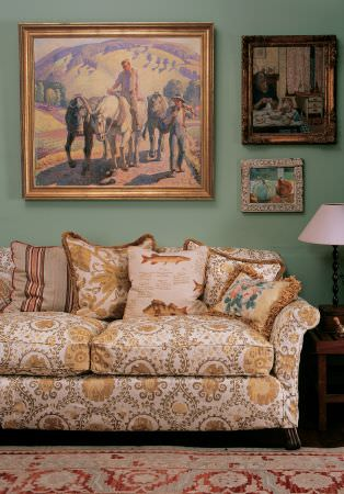 Lewis and Wood -  Lewis And Wood Fabric Collection - A white, gold and grey patterned sofa and scatter cushions,with a red and cream rug, framed paintings and a small table