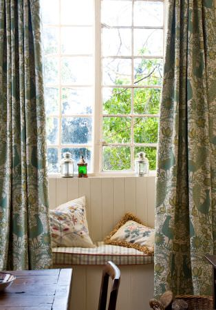 Lewis and Wood -  Lewis And Wood Fabric Collection - Busy patterned curtains in blue, green and white,with a checked window seat, patterned cushions, a wooden table and a chair