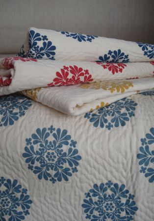 Lewis and Wood -  Lewis And Wood Fabric Collection - Simple, circular floral designs on folds of white fabric, with one in dusky blue, one in gold, one in red, and one in navy