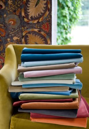 Lewis and Wood -  Lewis And Wood Fabric Collection - A patterned backdrop behind a kiwi green coloured sofa with folded fabrics in plain colours such as blue, grey and pink