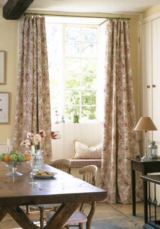 Lewis and Wood -  Lewis And Wood Fabric Collection - A large wooden table and chairs with glassware, grey, white and pink patterned curtains,black tables, a cushion and a lamp