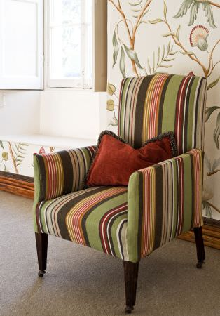 Lewis and Wood -  Lewis And Wood Fabric Collection - An armchair striped in green, red, gold and grey, with dark wood legs, a brick red cushion, and patterned wallpaper