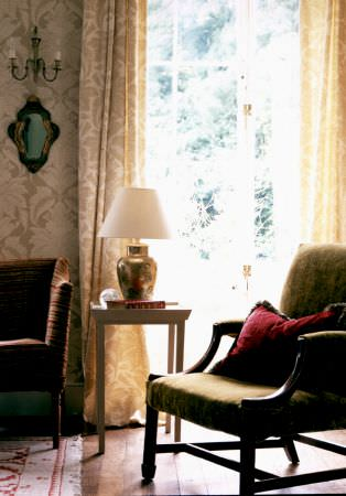 Lewis and Wood -  Lewis And Wood Fabric Collection - Light beige and cream patterned curtains and wallpaper, withan olive green and wood armchair, a red cushion and a cream table