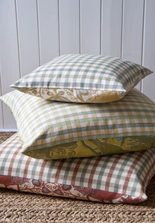 Lewis and Wood -  Lewis And Wood Fabric Collection - A stack of three square cushions, each with checks on one side and patterns on the other, in white, blue, green and red