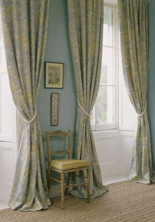 Lewis and Wood -  Lewis And Wood Fabric Collection - Pale shades of blue and green making up very long patterned curtains with white rope tiebacks, and a cream-beige chair