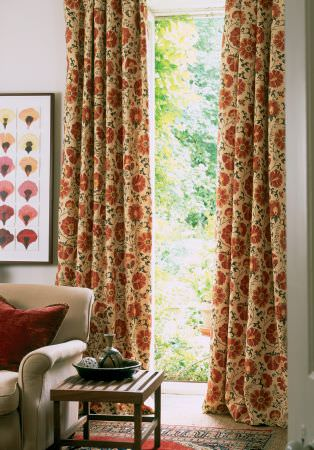 Lewis and Wood -  Lewis And Wood Fabric Collection - Red and cream floral patterned curtainsbehind abeige sofa, a dark red scatter cushion and a low wooden occasional table