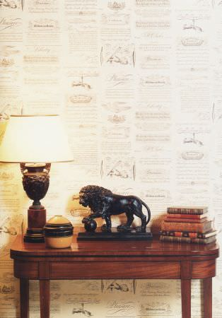 Lewis and Wood -  Lewis And Wood Fabric Collection - Wooden side table with a lion sculpture, a carved lamp with white shade,a pot, a stack of books and a patterned backdrop