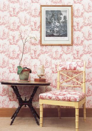 Lewis and Wood -  Lewis And Wood Fabric Collection - Red and white patterns on wallpaper and the seat cushion of a cream-yellow chair,with a wooden table, vases and a picture
