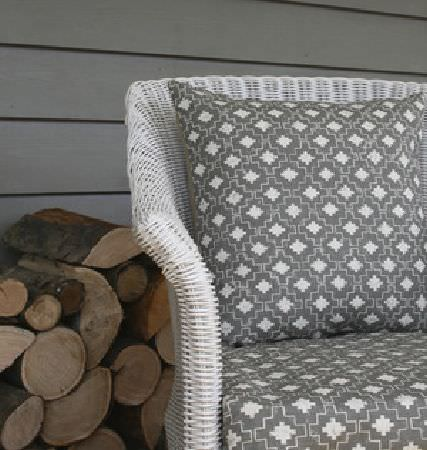 Lindsay Alker -  Lindsay Alker Fabric Collection - A stack of logs behind a white wicker armchair, with smoke grey and white geometric print seat and back cushions