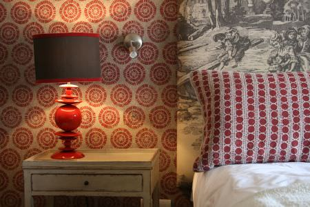 Lindsay Alker -  Lindsay Alker Fabric Collection - A grey and red lamp ona distressed side table, with red and cream walls,a patterned headboard, and circle print cushions