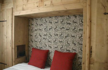 Lindsay Alker -  Lindsay Alker Fabric Collection - Plain wood cupboards surrounding a bedwith white bedding and 2 bright red scatter cushions, with grey deer print walls
