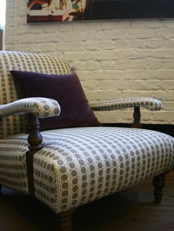 Lindsay Alker -  Lindsay Alker Fabric Collection - Rows of circles made in grey and white, covering an elegant armchair with wooden legs, with aplain dark purple cushion