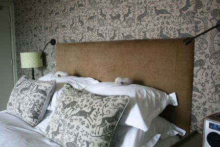 Lindsay Alker -  Lindsay Alker Fabric Collection - A light brown headboard to a bed with white bedding andgrey deer print cushions, with matching wallpaper and 3 lamps