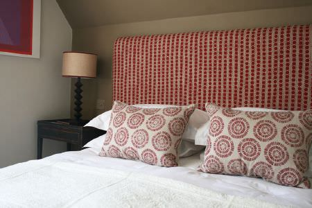 Lindsay Alker -  Lindsay Alker Fabric Collection - White sheets and pillows on a bed with a red and beige headboard and co-ordinating cushions, beside a black table and a lamp