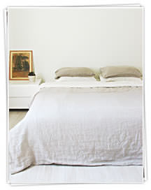 Ada and Ina -  Linen Fabrics Collection - A white duvet and quilt with brown duvets in a simple bedroom