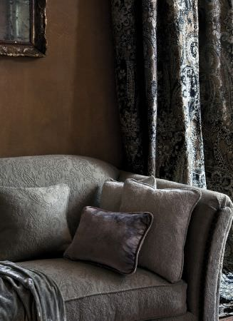 Lizzo -  Aberdeen Fabric Collection - Grey sofa covered in subtle grey embroidered pattern, with matching cushion, three plain cushions, silver velvet, and patterned curtains