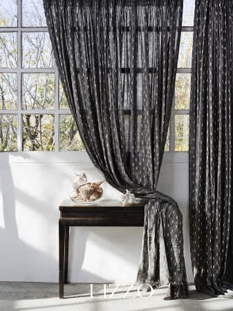 Lizzo -  Aroma Fabric Collection - Thin curtains made of lightweight, dark grey fabric with white dashes, next to a black side table with a glass bowl filled with shells