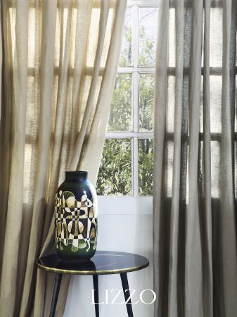 Lizzo -  Aroma Fabric Collection - A round black occasional table with a black vase covered in a beige geometric print, with thin beige curtains and thin grey curtains