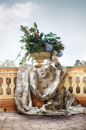 Lizzo -  Botanical Fabric Collection - Mediterranean style wide gold vase, draped with grey, cream and pewter coloured fabric in a floral pattern