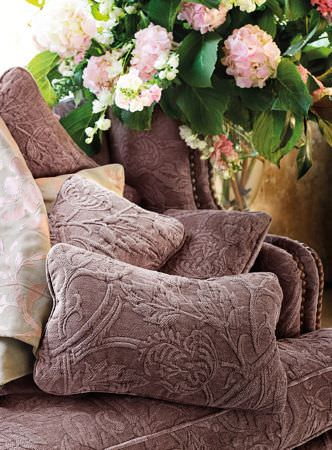 Lizzo -  Botanical Fabric Collection - Sofa and scatter cushions (rectangular and square) in a plain purple colour, but with a raised, textured floral pattern, with floral fabric