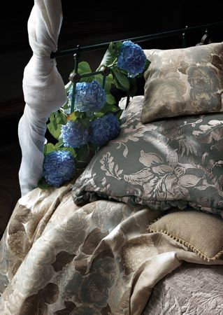 Lizzo -  Botanical Fabric Collection - Black metal bedframe wrapped in thin white fabric, with a blue and silver cushion, blue, grey and brown fabric, and a matching cushion