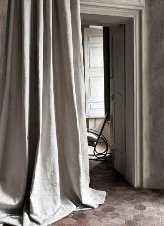 Lizzo -  Capri Fabric Collection - White-grey curtains with an almost imperceptible pattern, in front of a rocking chair with curved metal bars for arms and legs and a cushion