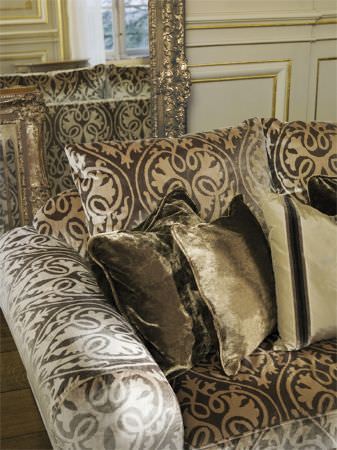 Lizzo -  Ducale Fabric Collection - Sofa covered in a large print of brown and cream swirls, with gold velvet cushions,cream and black striped cushions, and gold-framed mirrors