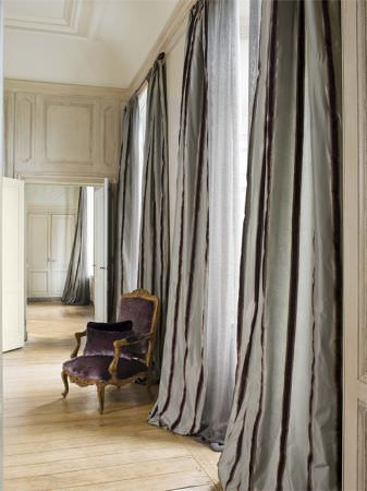 Lizzo -  Ducale Fabric Collection - Pale duck egg blue curtains with narrow dark stripes, beside an armchair with a gold wood frame, and purple padding and matching cushion