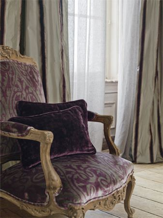 Lizzo -  Ducale Fabric Collection - Ornately carved wood chair with seat and back covered in purple and grey patterned fabric, with purple velvet cushions and striped curtains