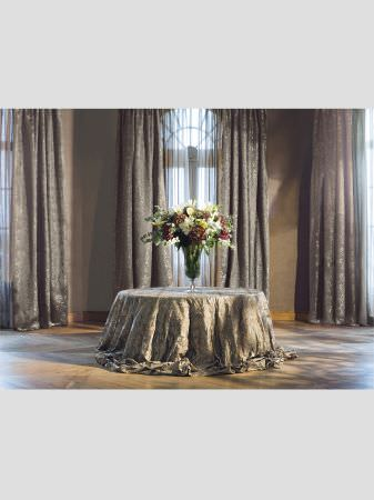 Lizzo -  Ducale Fabric Collection - Round table covered with subtly patterned grey, textured fabric, with floor-length curtains in the same fabric, and a large glass vase