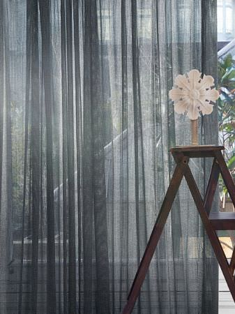 Lizzo -  Forest Fabric Collection - Plain dark wood ladder with simple wooden flower sculpture, in front of a curtain of denim blue coloured see-through fabric