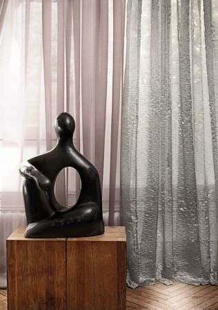 Lizzo -  Forest Fabric Collection - Black stone human figure sculpture on brown wood blocks, in front of plain beige and silvery blue translucent fabric curtains