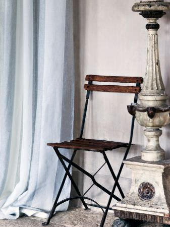 Lizzo -  Formentera Fabric Collection - Folding chair with a black metal frame and slats of wood for the seat and back, with a large carved sculpture, and plain, pale blue curtains