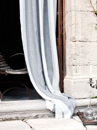 Lizzo -  Formentera Fabric Collection - Wooden-slatted curving chair, next to long, striped grey and white fabric, with a tiny glass cup and a small, clear glass vase