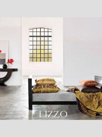 Lizzo -  Ikebana Fabric Collection - Bench seat with square black sides and base, thick grey seat cushion, gold, orange, purple cushions, gold fabric, side table and round vase
