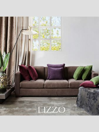 Lizzo -  Ikebana Fabric Collection - Brown three seater sofa with blue-grey velvet footstool, red, purple and green cushions, low table, black printed vase and beige curtains