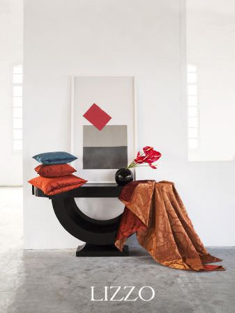 Lizzo -  Ikebana Fabric Collection - Black semi-circle with flat top to make a side table with orange patterned fabric, orange, red and blue satin cushions, and round black vase