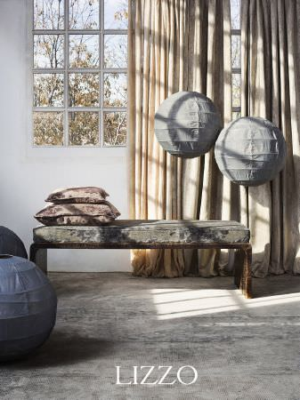 Lizzo -  Ikebana Fabric Collection - Spherical paper lampshades in grey, with cream curtains, a simple wooden bench with grey patterned seat cushion and brown patterned cushions