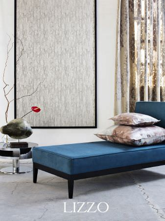 Lizzo -  Ikebana Fabric Collection - Plain blue chaise longue on black base, with cream and grey patterned wall hanging, brown patterned cushions, round silver table, sculpture