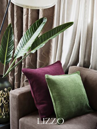 Lizzo -  Ikebana Fabric Collection - Plain burgundy cushion with plain green cushion on mocha coloured sofa, with brown patterned curtains, beige curtains and geometric vase
