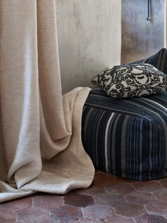 Lizzo -  Java Fabric Collection - A stack of satin cushions in grey, white, red, yellow and blue in a low key setting