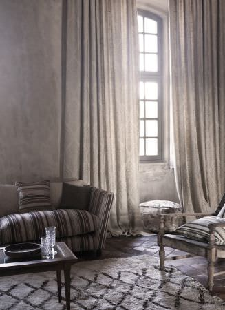 Lizzo -  Java Fabric Collection - Wood and glass coffee table, distressed wood table, striped sofa, cushions, cream patterned curtains, round grey velvet footstool, grey rug