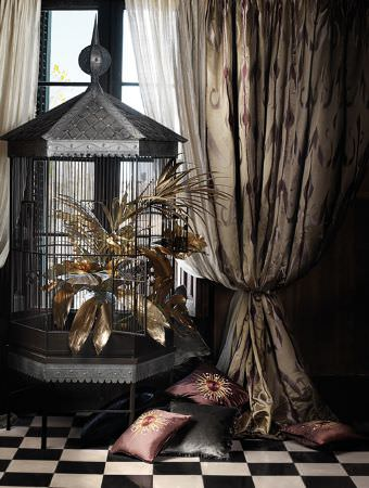 Lizzo -  Maharaja Fabric Collection - Tall hexagonal black and silver bird cage with a pointed roof and a spire, with cream patterned curtains, purple cushions and a grey cushion