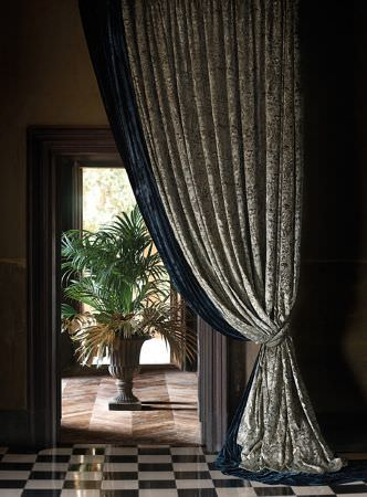 Lizzo -  Maharaja Fabric Collection - Large stone urn, with tied back curtains in a luxurious deep blue fabric, and pale cream-grey fabric with a small, detailed pattern
