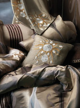 Lizzo -  Maharaja Fabric Collection - Champagne coloured cushion and curtain with silver and gold embroidery, matching fabrics with grey patterns and dark stripes, brown cushion