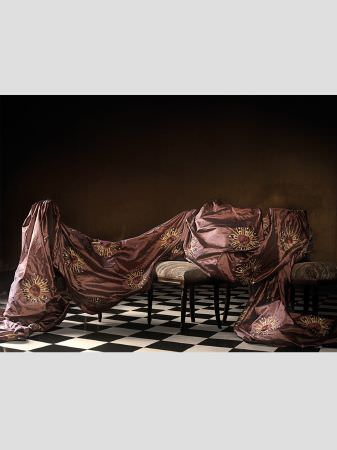Lizzo -  Maharaja Fabric Collection - Swathe of rich red-purple satin effect fabric with god embroidery in a sun shape, draped across dark wood chairs with grey-beige seats