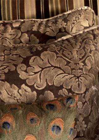 Lizzo -  Mata Hari Fabric Collection - Three cushions in brown and gold; one striped, two with a textured leafy swirl pattern. Also with one embroidered peacock feather cushion