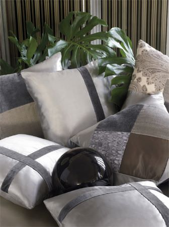 Lizzo -  Mata Hari Fabric Collection - Patchwork and panelled cushions in white, grey, silver, cream and beige fabrics, all with different textures, and with a shiny black ball