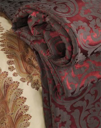 Lizzo -  Mata Hari Fabric Collection - Blanket in matt grey and shiny red fabric with large, leafy swirl patterns, with a detailed orange and green pattern printed on cream fabric
