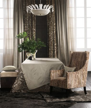 Lizzo -  Mata Hari Fabric Collection - Ivory tablecloth, cream and brown patterned tablecloth, both with matching curtains, a patterned armchair, voile, and cube seat with cushion